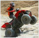 man riding ATV on 2 wheels