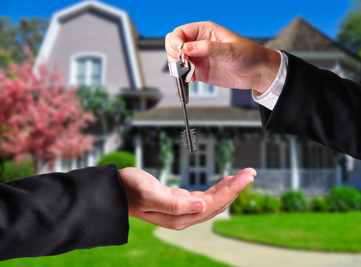 a Realtor handing keys to the new owner of a home