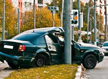a car that has been involved in an accident up against a pole
