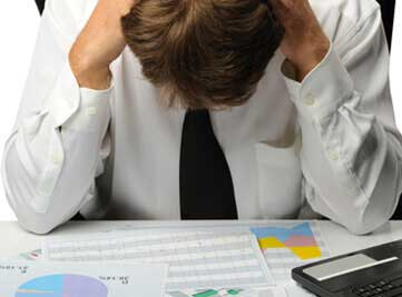 a man appears worried looking at financial documents