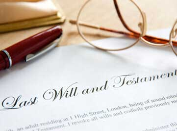 a last will & testament with glasses and a pen