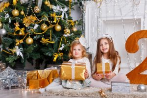 girls sitting under Christmas tree with gifts